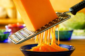 Cheddar being grated with a coarse grater