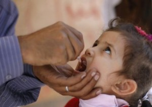 A girl receives a drop of polio vaccine at a health center in Sanaa
